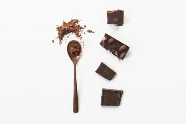Trozos de chocolate puro con almendras junto a una cuchara con chocolate en polvo sobre fondo blanco. Poppyns Magazine