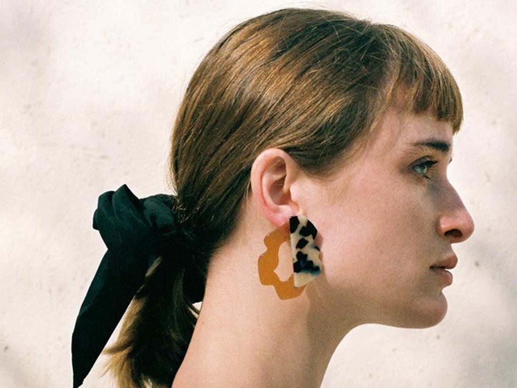 Mujer rubia de perfil con flequillo, coleta y pendientes de acetato moteado de Apres Ski. Poppyns Magazine
