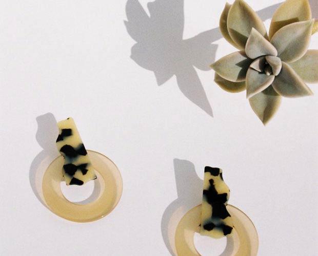 Pendientes de acetato amarillo traslúcido y moteado de Après Ski sobre fondo claro y una planta. Poppyns Magazine