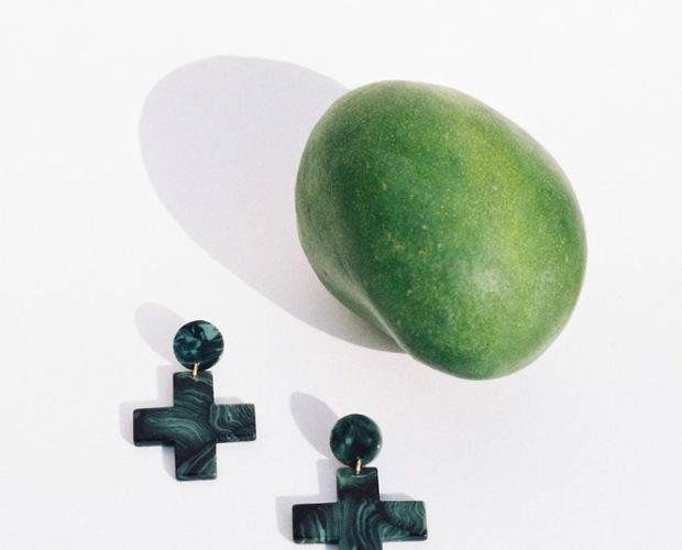 Pendientes de acetato azul marino y azul mar de Après Ski sobre fondo claro y una manzana verde. Poppyns Magazine