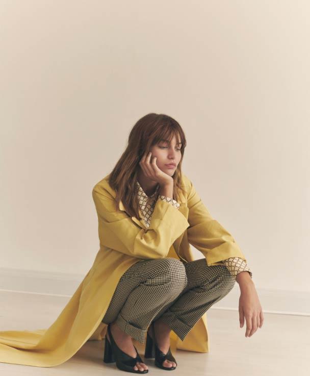 Mujer joven rubia con flequillo de cuclillas y la cabeza apoyada en su mano, con zapato negro con tacón, pantalón a cuadros, camisa retro y chaqueta amarilla tres cuartos de Momoni. Poppyns Magazine