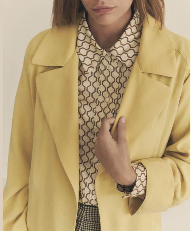 Mujer joven rubia vistiendo camisa retro y americana amarilla de Momoni con la mano en la solapa. Poppyns Magazine