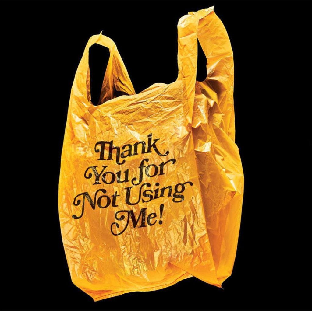 Bolsa de plastico amarilla con texto thank you for not using me impreso en negro y fondo negro. Poppyns Magazine