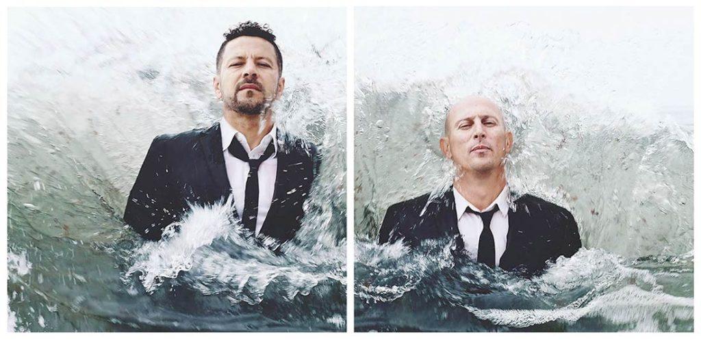Hombres con traje de chaqueta negro, corbata negra y camisa blanca saliendo del agua. Poppyns Magazine