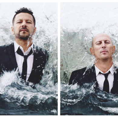 Hombres con traje de chaqueta negro y corbata negra saliendo del agua. Poppyns Magazine