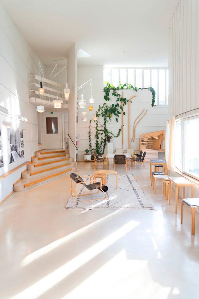 Estancia blanca con techos altos, una alfombra en el suelo, mobiliario de madera, ventanales en una pared curva, una enredadera verde al fondo, una escalera y lámparas blancas colgadas del techo. Poppyns Magazine