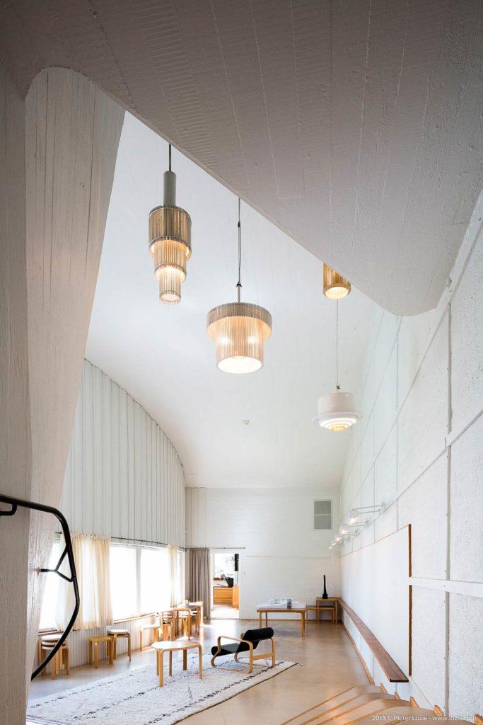 Estancia blanca con techos altos, una alfombra en el suelo, mobiliario de madera, ventanales en una pared curva, una pizarra larga y lámparas con lamas de madera colgadas del techo. Poppyns Magazine
