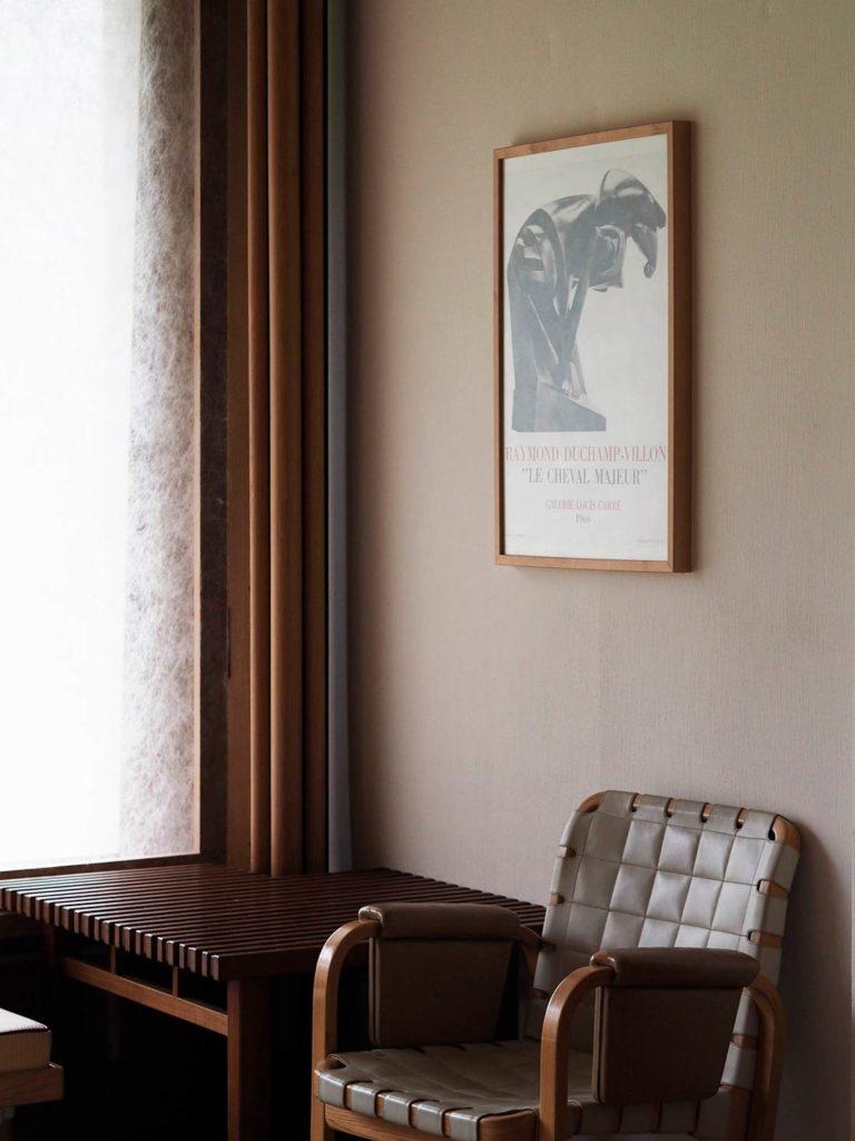 """Estancia con un sillón de madera y cuero, una mesa auxiliar de madera y un cuadro en la pared con las letras Raymond Duchamp Villon """"Le Cheval Majeur"""". Poppyns Magazine"""