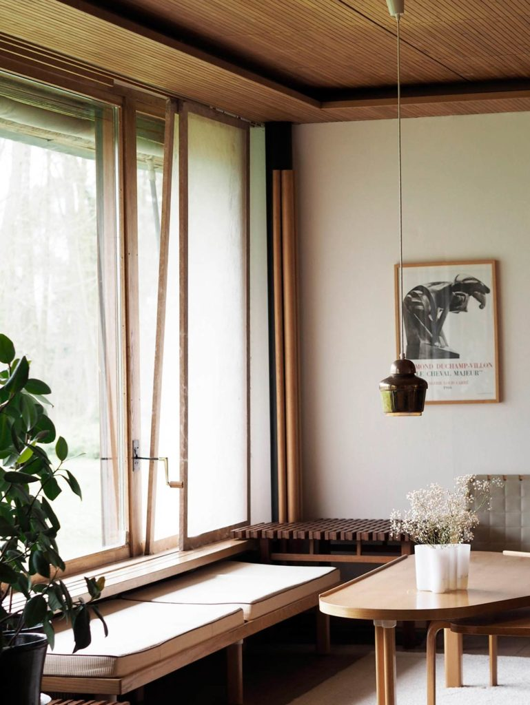 Sala de estar con mobiliario de madera, techo de madera, una lámpara colgante, un florero y una planta. Poppyns Magazine