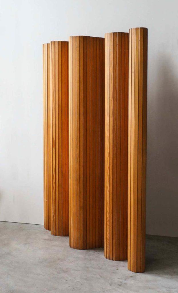 Estructura de lamas de madera formando una figura ondulada. Poppyns Magazine