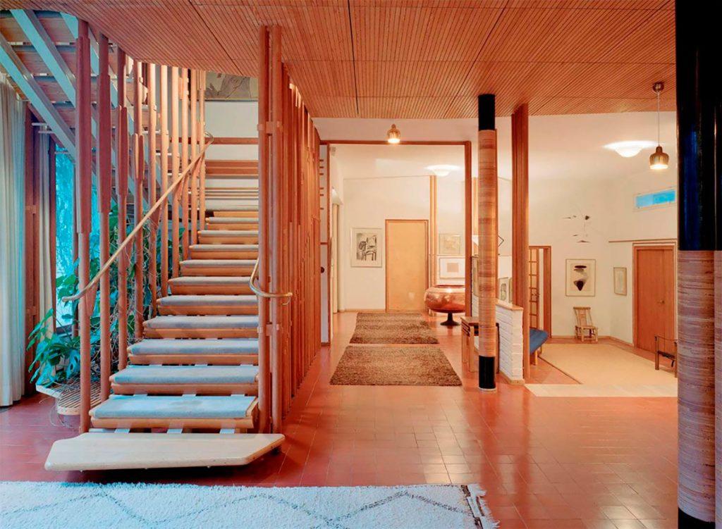 Interior de una vivienda de diseño, con suelo adoquinado color teja, escalera de madera con peldaños enmoquetados, pasamanos de cobre, techo de madera, alfombras y vegetación. Poppyns Magazine