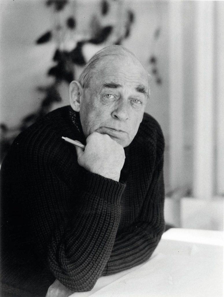 Foto retrato en blanco y negro de Alvar Aalto, sentado apoyando sus brazos sobre la mesa, con un lápiz en la mano y mirando a la cámara. Poppyns Magazine
