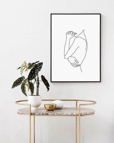 Ilustración en negro sobre fondo blanco del torso de una mujer. La ilustración está colgada de una pared beige junto con una mesa auxiliar de estructura tubular de bronce y superficie de mármol. Poppyns Magazine