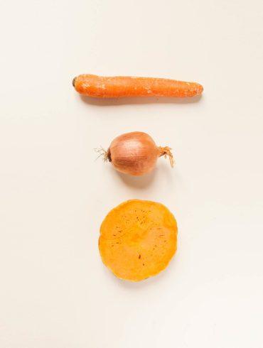 Foto cenital de una zanahoria, una cebolla y media calabaza. Poppyns Magazine