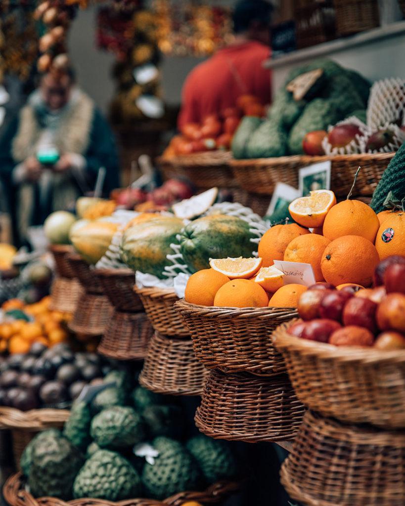 Parada de un mercado con cestas de mimbre con naranjas, aguacates, mangos y otra fruta y verdura. Poppyns Magazine