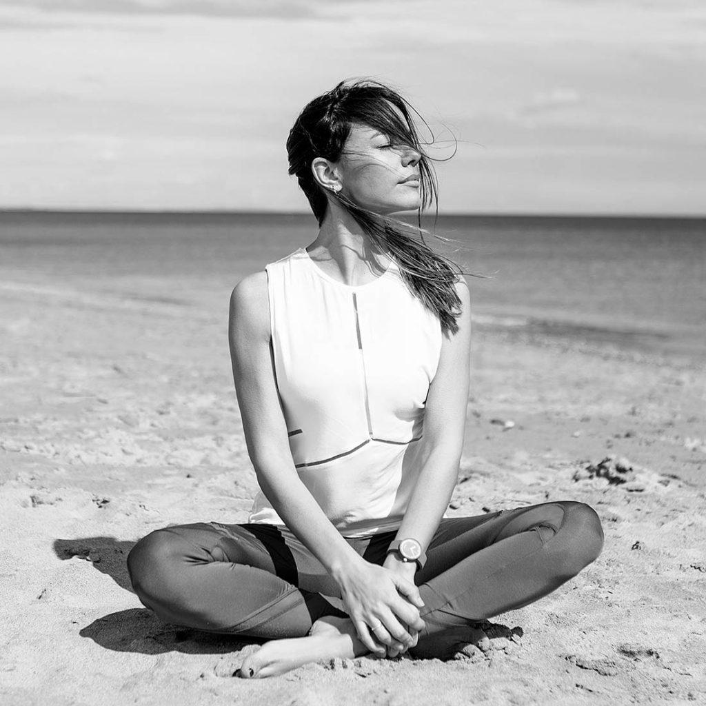 Chica joven morena sentada en la playa sobre la arena, con las piernas cruzadas, los ojos cerrados tomando el sol, el pelo sobre la cara y el mar de fondo.