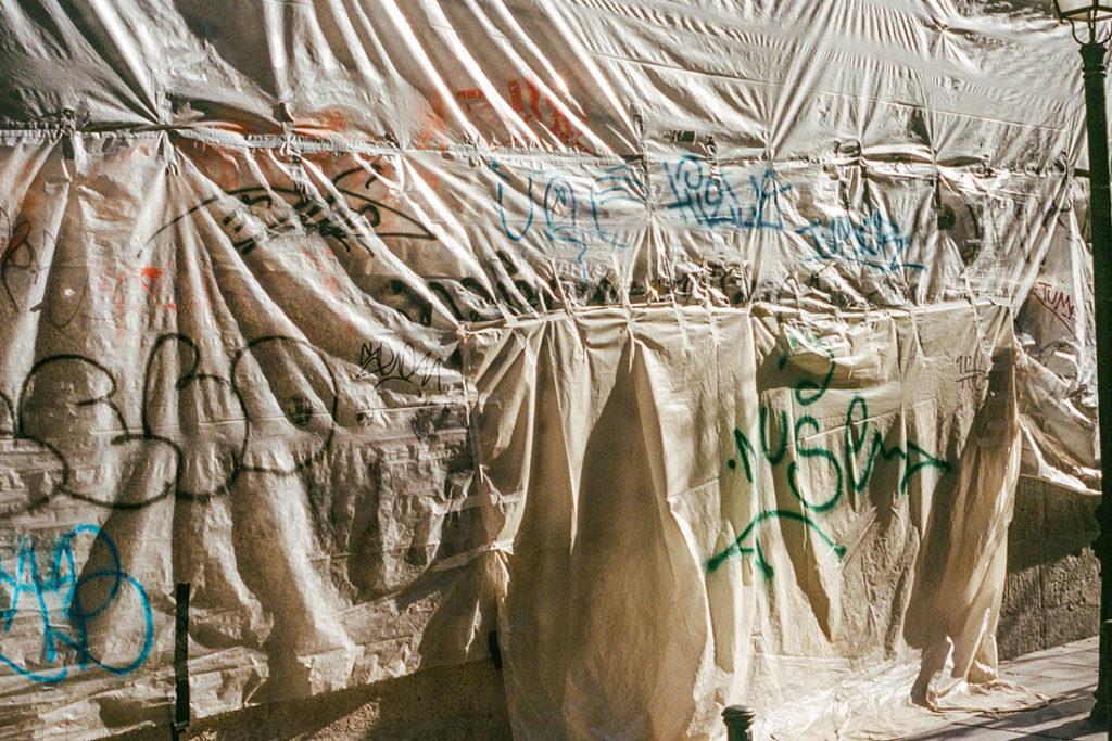 Grafitis sobre lonas de plástico cubriendo una fachada. Poppyns Magazine