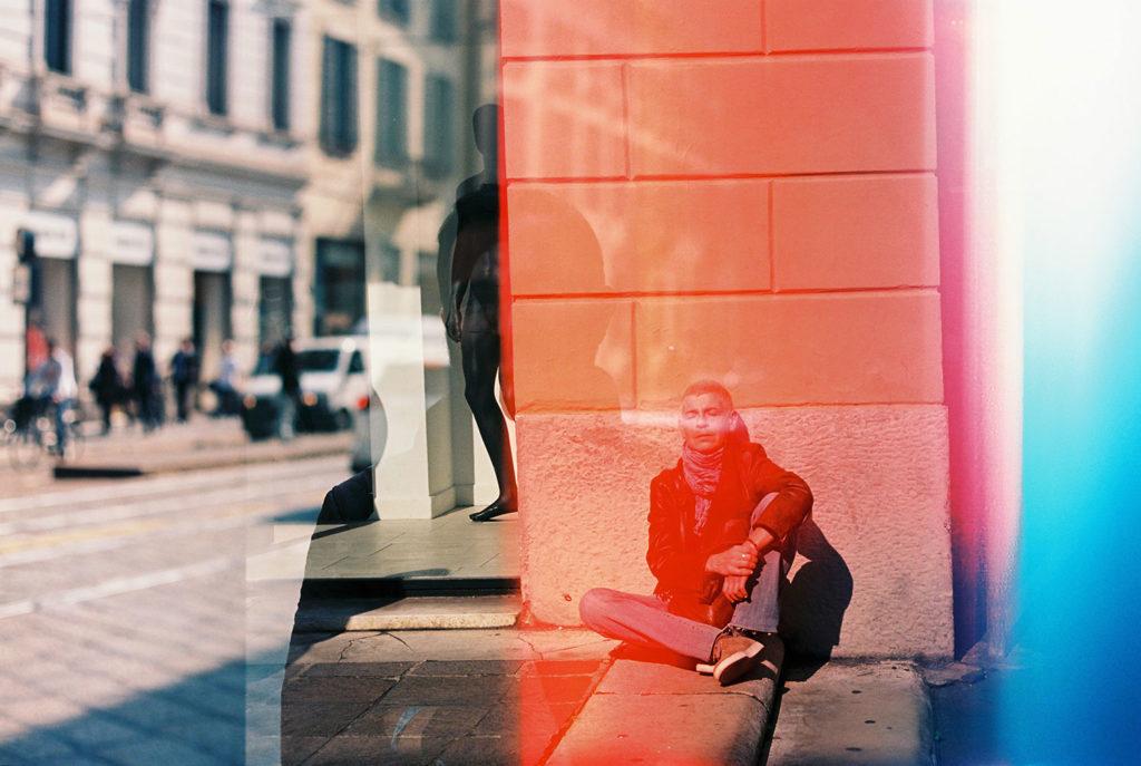 Foto con reflejo en un cristal con un hombre bien vestido sentado en el suelo de la calle con los ojos cerrados y el sol dándole en la cara y la silueta de otro hombre reflejada en el cristal tras una franja roja. Poppyns Magazine