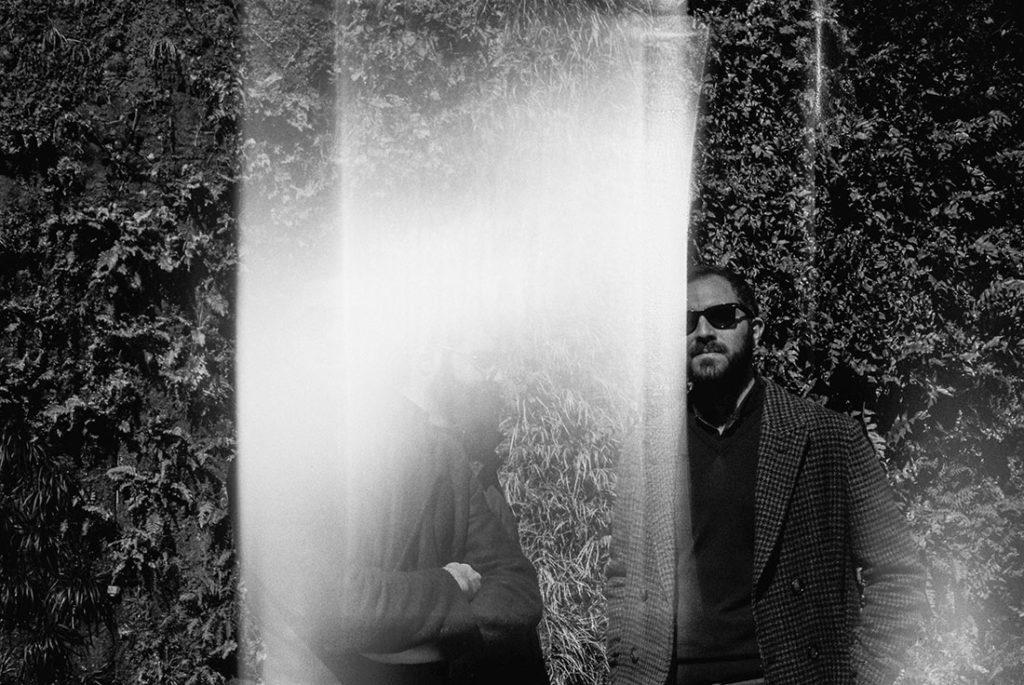 Foto en blanco y negro de dos hombres con americana y gafas de sol sobre pared con vegetación, con un efecto de quemado en la parte central de la foto. Poppyns Magazine