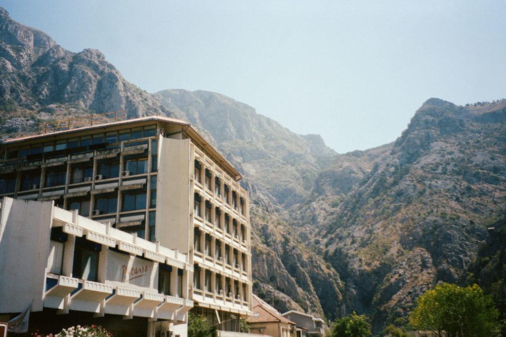 Foto de un edificio de fachada blanca y un letrero que pone Picasso, con montañas al fondo y cielo azul despejado. Poppyns Magazine