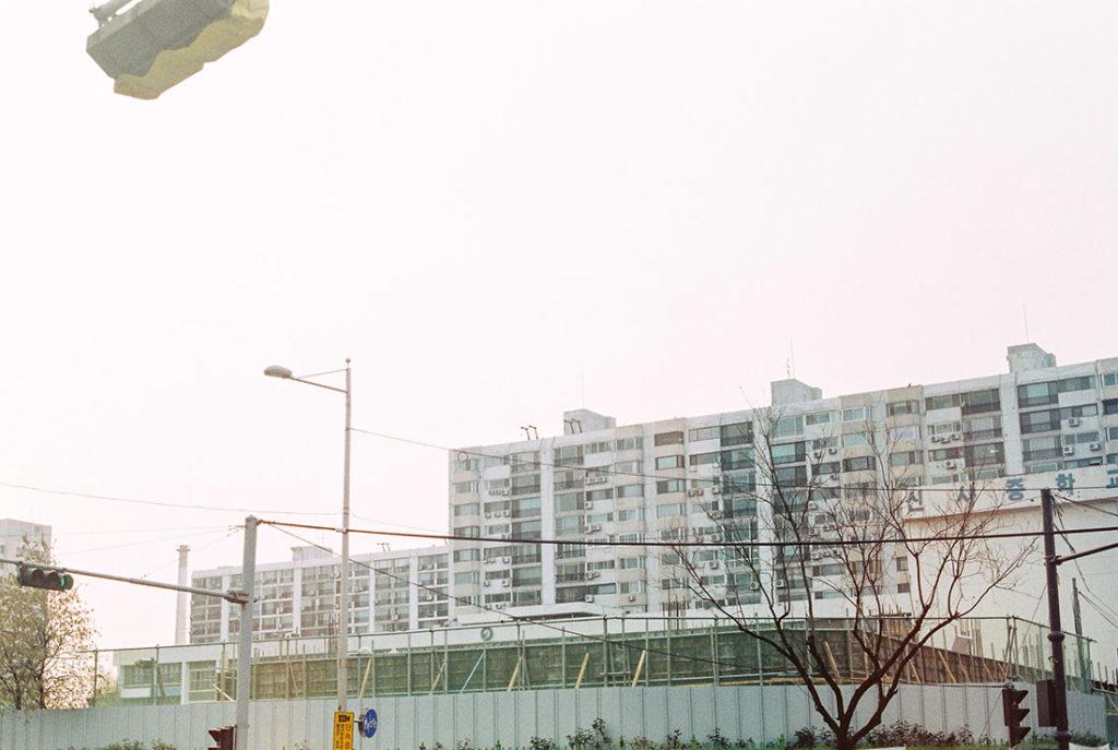 Bloque de edificios de fachada blanca con máquinas de aire acondicionado en la fachada. Poppyns Magazine