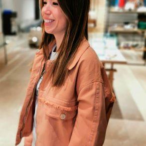 Chica joven morena de perfil, sonriendo, con una chaqueta vaquera de color salmón, pantalón blanco y fondo difuminado. Poppyns Magazine
