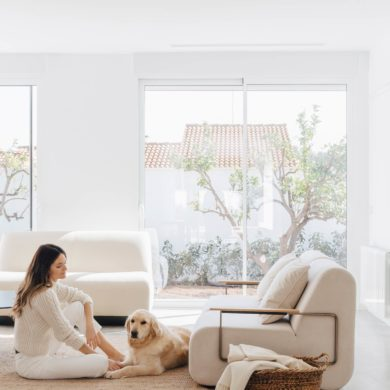 Salón minimalista con muebles de diseño, un cesto de mimbre con mantas, una mujer sentada sobre una alfombra junto a un perro golden blanco y un ventanal con un jardín al fondo. Poppyns Magazine