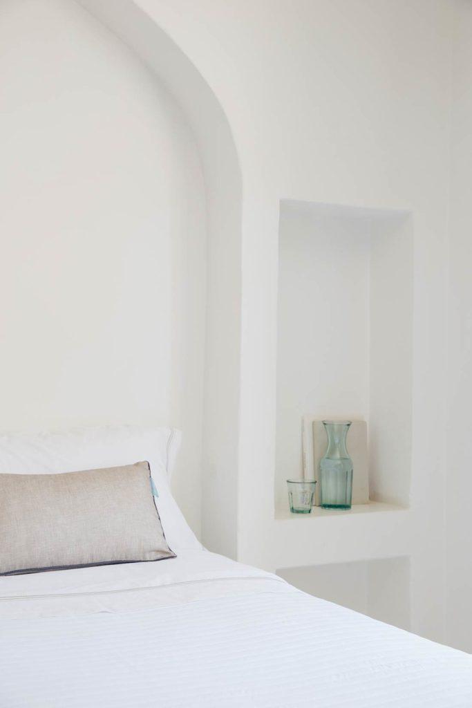 Dormitorio blanco minimalista con una cama con colcha blanca, una estantería de obra y una jarro y un vaso de cristal, sobre una balda. Poppyns Magazine