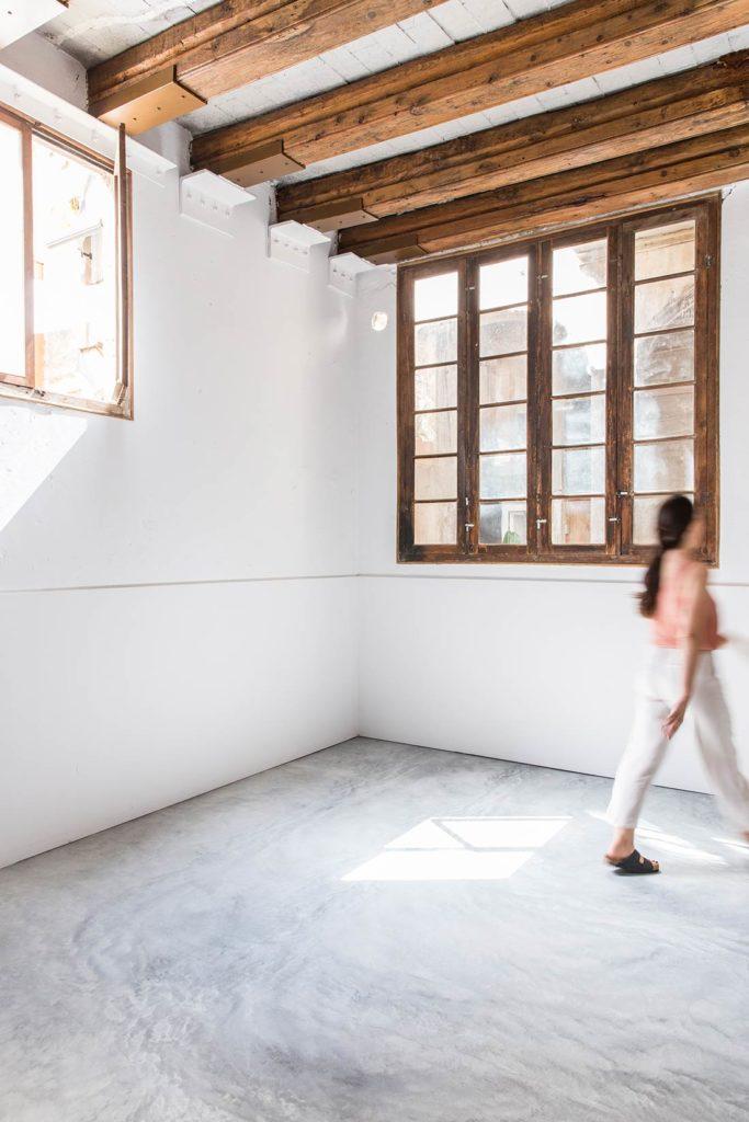 Habitación diáfana con techo con vigas de madera, ventanales de madera, suelo de cemento y una mujer andando difuminada. Poppyns Magazine