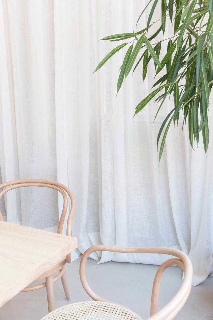 Sillas de madera con asiento de rejilla, junto con una mesa de madera, una cortina blanca de lino y una planta. Poppyns Magazine