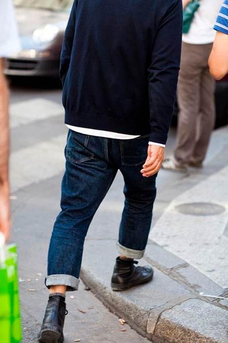 Persona caminando con vaqueros arremangados, botas negras y cardigan azul marino. Poppyns Magazine