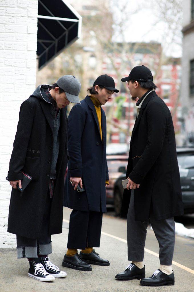 Hombres asiáticos bien vestidos parados en la calle mirando al suelo, vistiendo chaquetón tres cuartos de color oscuro, pantalón vaquero y gorra. Poppyns Magazine