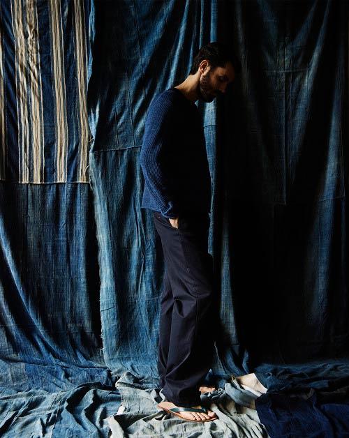 Hombre moreno y con barba posando de perfil sobre un fondo de telas vaqueras cosidas, vistiendo un pantalón chino azul marino y un suéter azul marino de punto. Poppyns Magazine