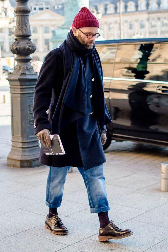 Hombre con barba y gafas de pasta redondas, andando por la calle vistiendo un pantalón vaquero arremangado, calcetines azul marino moteados de caña alta, zapato negro de cordón, chaqueta tres cuartos cruzada, bufanda azul marino, guantes beige y gorro de lana granate. Poppyns Magazine