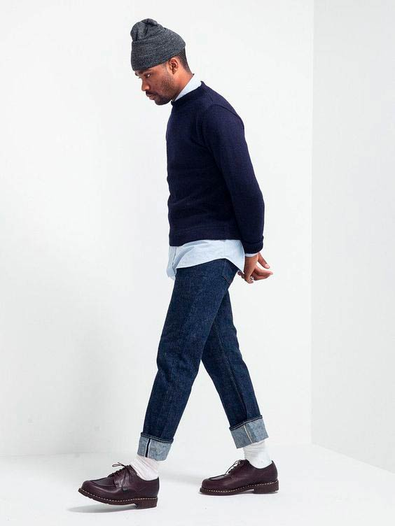 Persona de color posando de perfil con un pantalón vaquero arremangado, calcetines blancos, zapatos negros de cordón, camisa azul, suéter azul marino de punto y gorro gris marengo. Poppyns Magazine