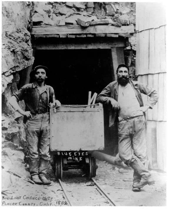 Foto en blanco y negro de dos mineros apoyados en un vagón de carbón. Poppyns Magazine