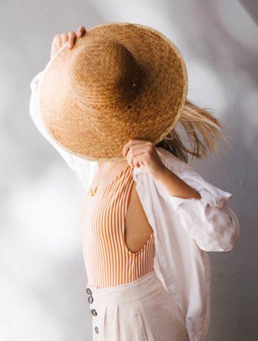 Mujer rubia con un bañador de rayas, pantalón de lino beige y camisa de lino blanca, tapándose el rostro con un sombrero de mimbre. Poppyns Magazine.