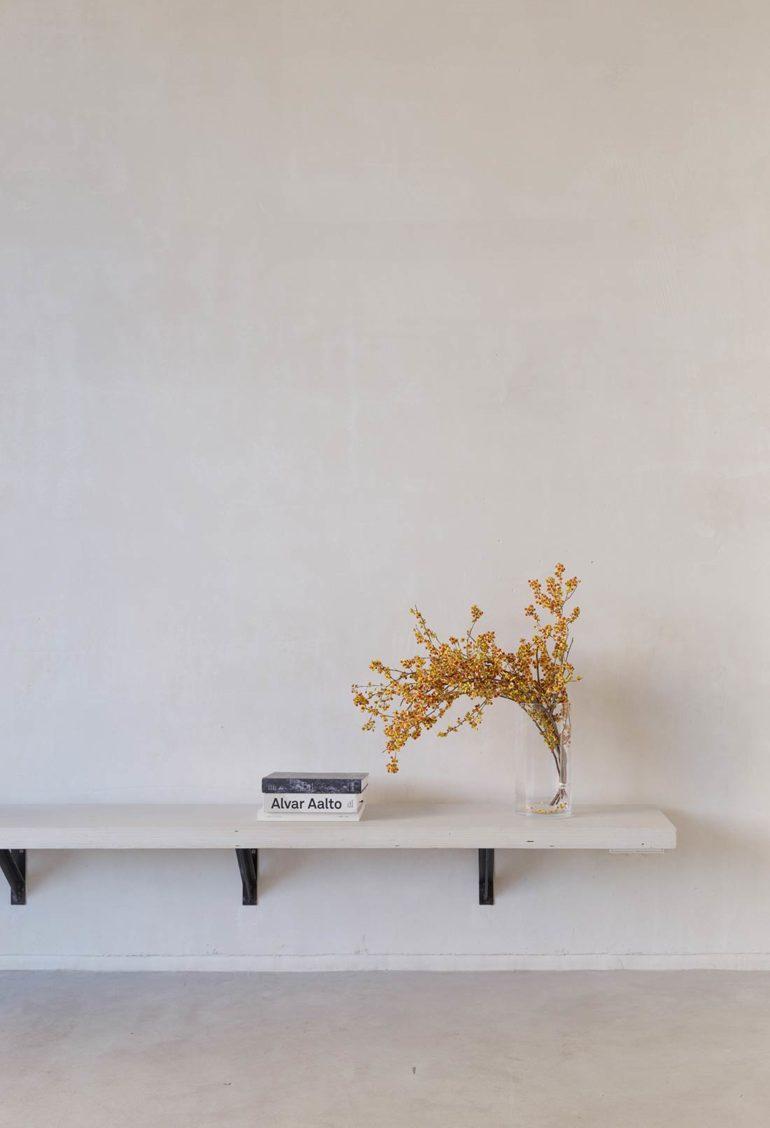 Banco de madera lacado en blanco con visagras negras empotrado a una pared color crema y suelo de cemento. Encima del banco hay unos libros donde en el lomo de uno de ellos dice Alvar Aalto, y un jarrón con un ramillete de hojas amarillas. Poppyns Magazine.