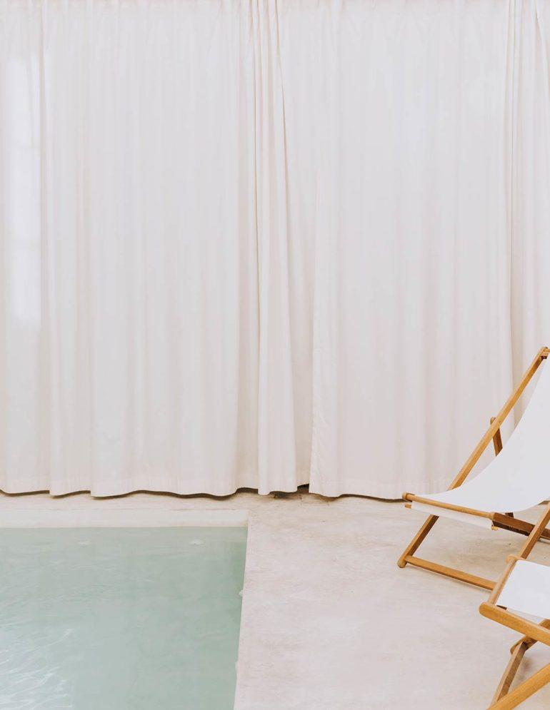 Habitación con una cortina de color beige, dos tumbonas de tela y estructura de madera, suelo de cemento y una piscina con agua cristalina. Poppyns Magazine.