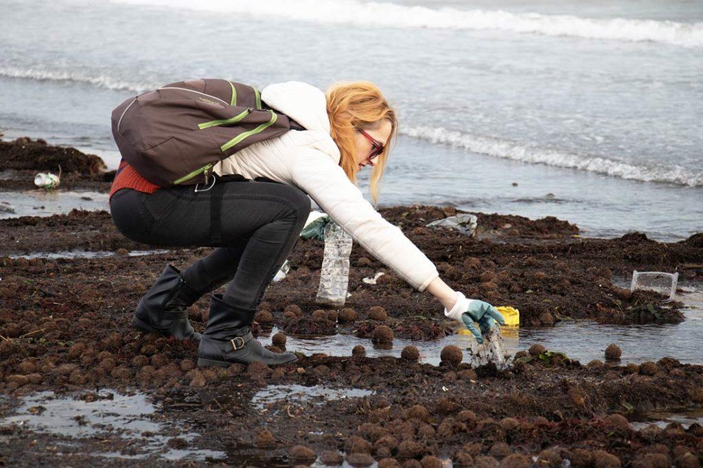 Mujer recogiendo plásticos en una playa. Poppyns Magazine