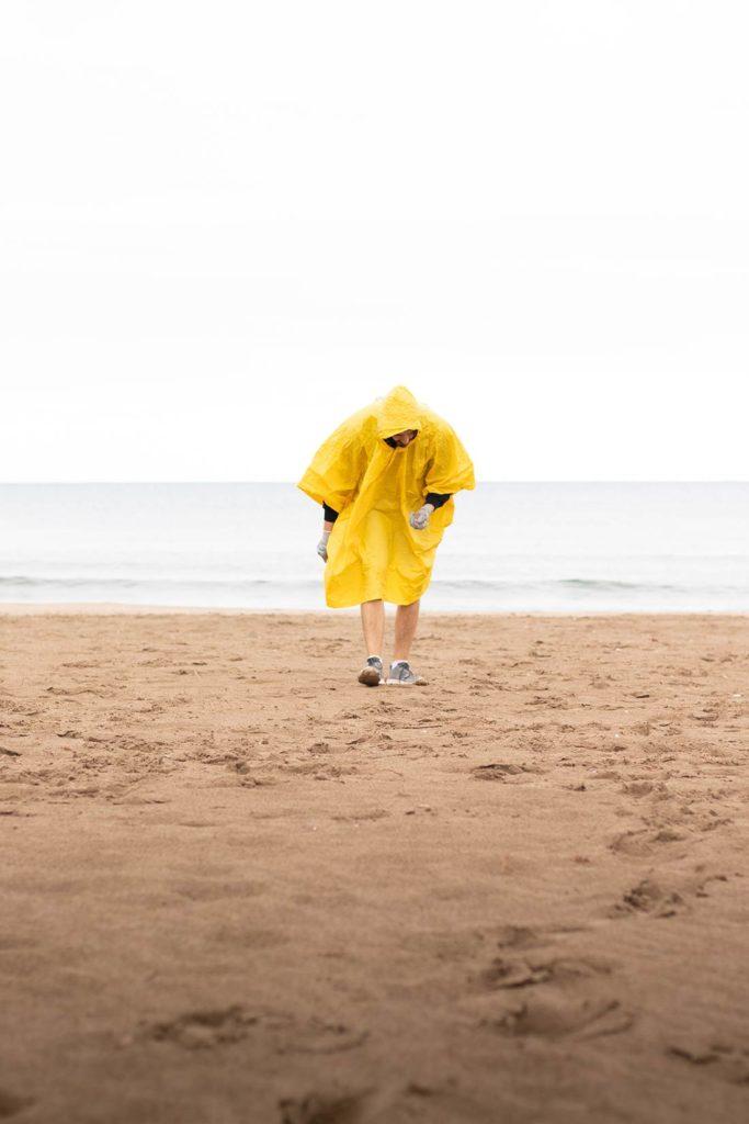 Persona andando por la playa con un chubasquero amarillo. Poppyns Magazine