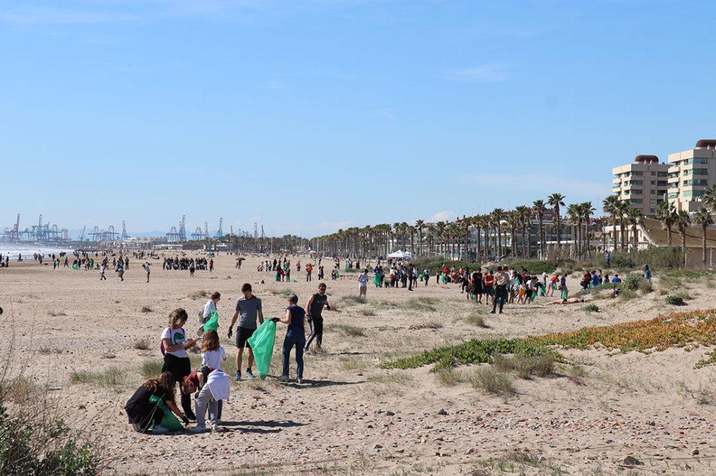 Personas recogiendo basura con bolsas de plástico verde en la arena de una playa. Poppyns Magazine