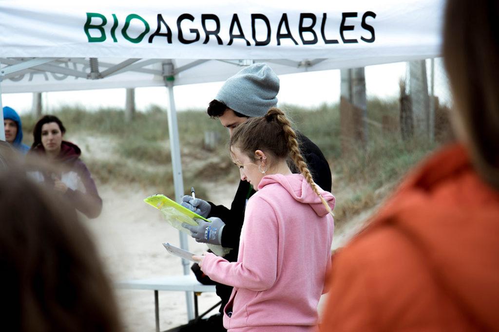 Chico y chica jóvenes tomando notas junto a una carpa blanca con un letrero rotulado con la palabra Bioagradables. Poppyns Magazine
