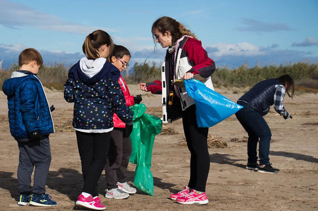 Niños recogiendo basura con bolsas de plástico verde y azul en la arena de una playa. Poppyns Magazine