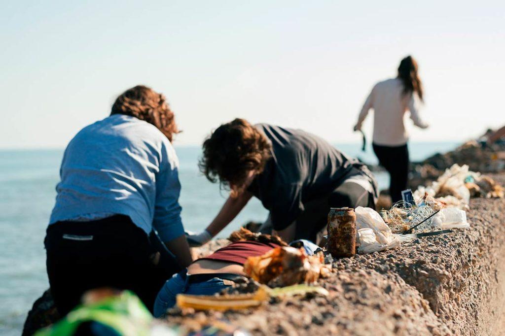Personas agachadas recogiendo residuos en la playa entre las rocas. Poppyns Magazine
