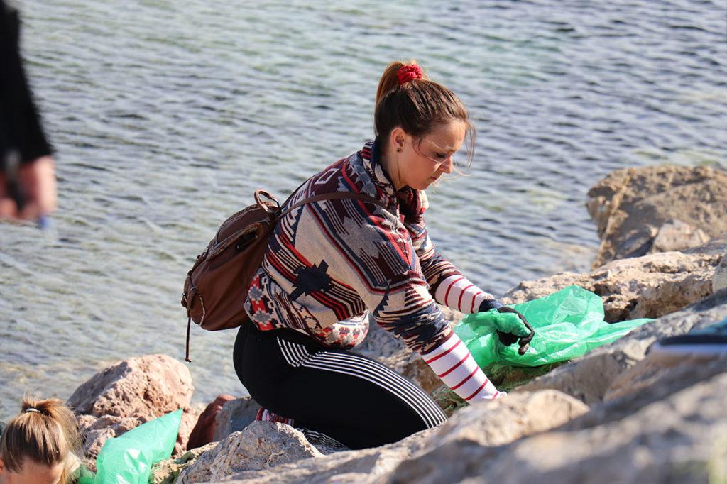 Chica joven agachada recogiendo residuos en la playa entre las rocas con una bolsa verde de plástico. Poppyns Magazine