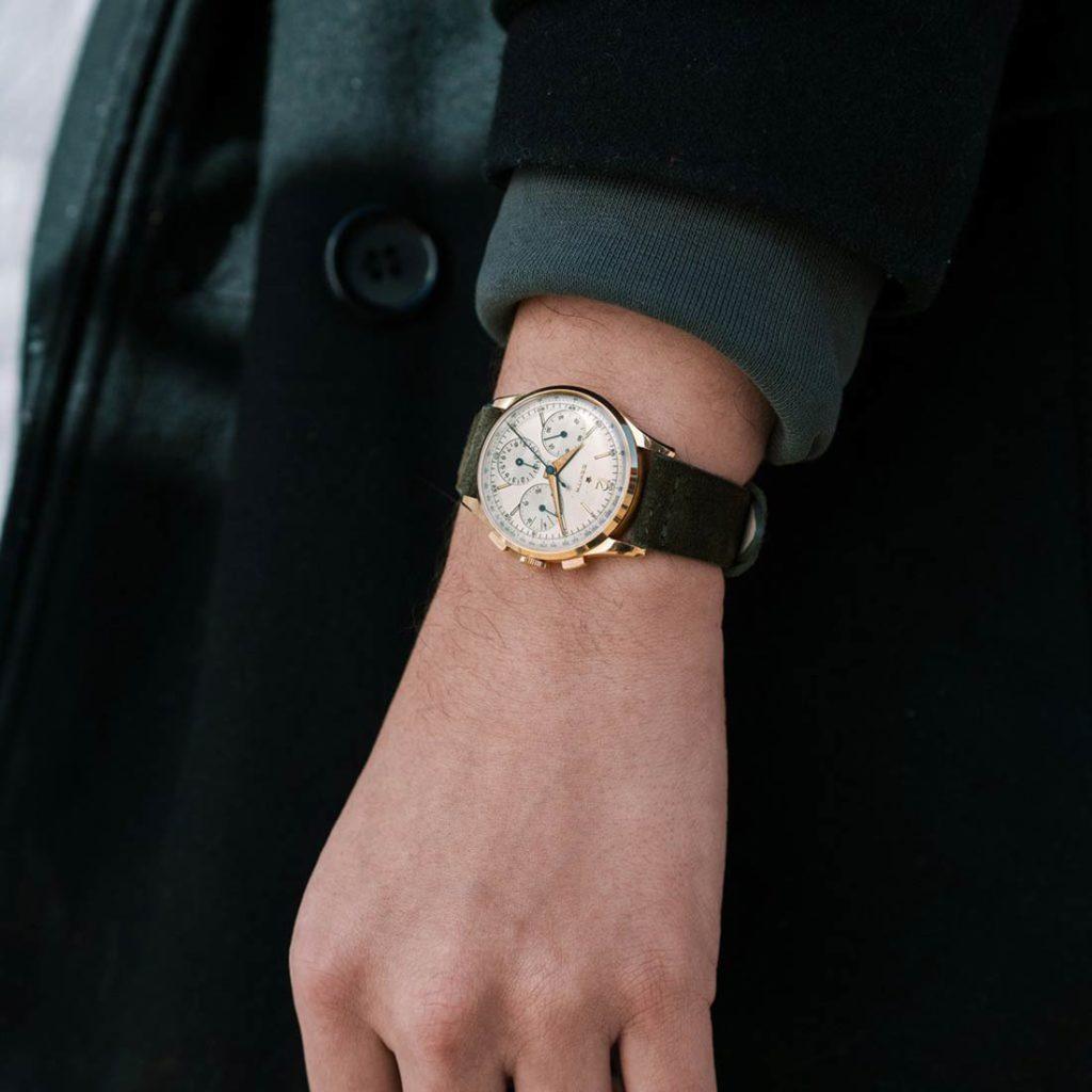Reloj de pulsera elegante con esfera blanca, borde dorado y correa de cuero verde. Poppyns Magazine