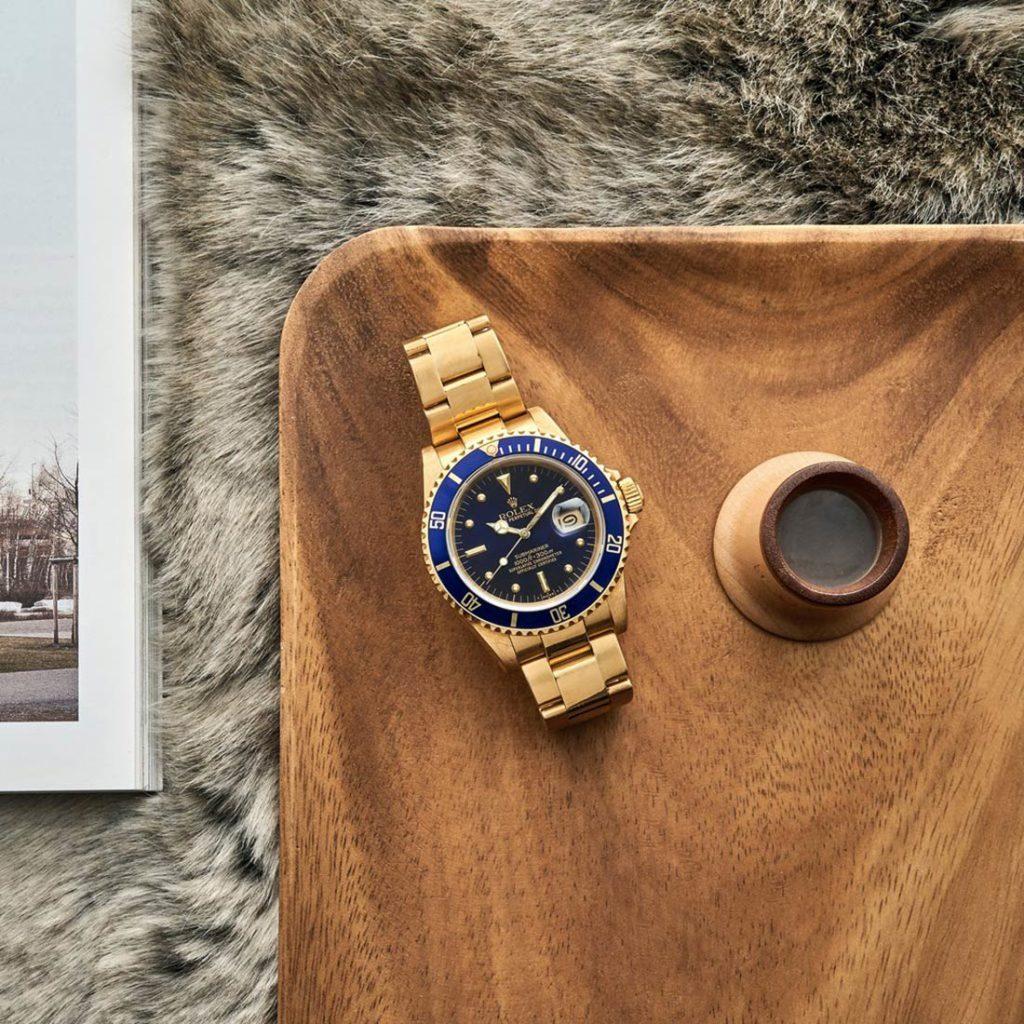 Reloj Rolex de oro con esfera azul marino sobre superficie de madera, una alfombra de pelo y una revista. Poppyns Magazine