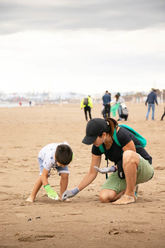 Mujer y niño recogiendo basura en una playa. Poppyns Magazine