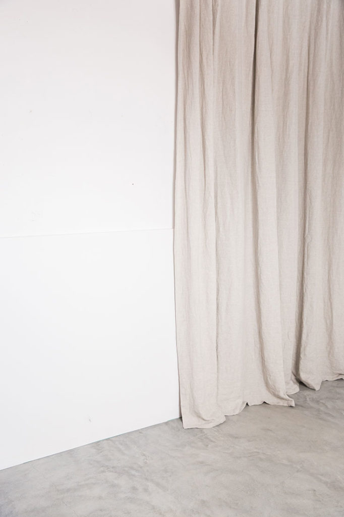 Cortina beige sobre pared blanca y suelo de microcemento. Poppyns Magazine